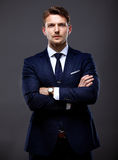Cool businessman standing on grey Royalty Free Stock Image