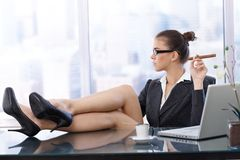 Cool businesswoman with feet up. On desk, wearing high heels, having coffee, cigar handheld, side view in skyscraper office Royalty Free Stock Image