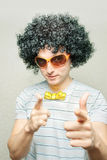 Cool casanova geek. Funny guy in afro curly wig with eyeglasses and ribbon bowtie pointing with his fingers stock photo
