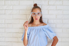 Cool Caucasial girl wearing paper glasses puckering lips Stock Images