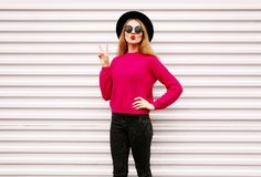 Cool cheerful girl blowing red lips sending sweet air kiss in colorful pink knitted sweater, black round hat. On white wall background stock photo