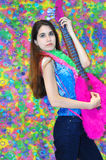 Cool Chick. Cool teenager holds funky pretend guitar and strikes a stren pose. Guitar is hot pink, fuzzy and is stuffed. Background is tye-dyed 70's style royalty free stock photo