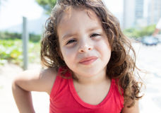 Cool child in a red shirt outside looking at camera. Cool child in a red shirt outside in a park with green plants in the background looking at camera Royalty Free Stock Image