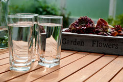 Cool, clear tap water. Three glasses with cool, clear tap water in it, standing on a wooden terrace table with plants at the background Stock Photos