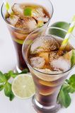 Cool cocktail rum and cola in glasses with bubbles and ice cubes, lime, mint in soft light white background, top view, closeup. Cool cocktail rum and cola in Royalty Free Stock Photo