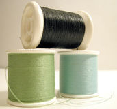 Cool Colored Thread. Black, green, and light blue thread on plastic spools Stock Photo