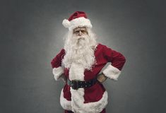 Cool confident Santa posing with arms akimbo royalty free stock photo