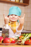 Cool cook. Little cook boy at kitchen showing cool gesture Stock Photo