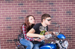 Cool Couple on Motorcycle in front of Brick Wall Royalty Free Stock Photography