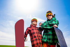Cool couple with snowboards in sport wear standing on the grass Royalty Free Stock Photography