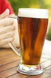 A Cool Cup of Beer. Refreshing, cool cup of beer in an outdoor restaurant, with nice foam Royalty Free Stock Photos