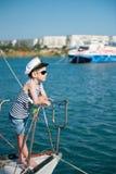 Cool cute little boy captain wearing sunglasses aboard luxury boat Stock Photos