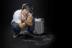 Cool DJ. A cool looking DJ / rapper chained to a DJ console showing a gang sign, on black studio background Stock Images