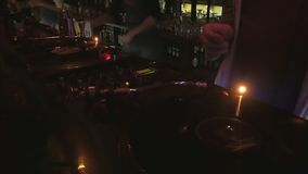 Cool dj behind the turntables performing in a bar
