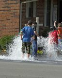 Cool Down. Children playing in water from fire hydrant Stock Image