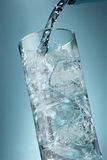 Cool drink. Cool carbonated water drink pouring into a tall glass with ice Stock Image