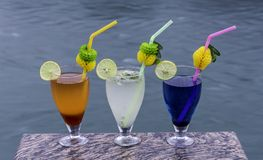 Cool drinks to freshen you up. Iced tea, lemon squash and blueberry drinks perched on a granite slab with river flowing in the background Royalty Free Stock Photography