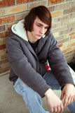Cool Dude. Sad teen boy with great hair by brick wall Royalty Free Stock Photography
