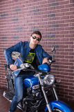 Cool dude sitting on his motorbike. In trendy modern sunglasses and a leather jacket leaning on the handlebars looking at the camera Royalty Free Stock Photo