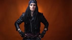 Cool edgy rocker with bandana on his head, spiked gloves, zips up his leather jacket. Young rocker man with long black hair, wearing bandana and leather gloves stock video footage