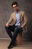 Cool elegant man sitting in studio Royalty Free Stock Photography