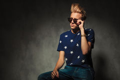 Cool fashion holding his sunglasses while sitting Stock Photo