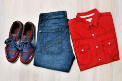 Cool fashion men`s casual outfit on wooden background, blue jeans pants, sneaker, top view Stock Images