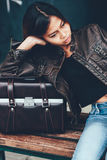 Cool Fashion style of young attractive girl in leather jacket and leather bag beside her. Girl in leather jacket and leather bag Royalty Free Stock Photos