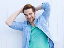 Cool fashionable guy smiling with hands in hair Royalty Free Stock Photography
