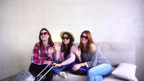 Female girls going on trip and preparing suitcases on couch in afternoon room. Cool female friends together collect large gray and blue suitcases, add up all stock footage