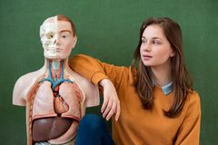 Cool female high school student portrait with an artificial human body model. Student having fun in Biology class. Education concept stock photography