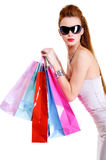 Cool female with shopping bags after shoppings. Portrait of the beautiful fashionable cool female with shopping bags after shoppings. Over white background royalty free stock photography
