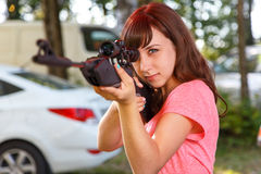 Cool female sniper aiming from telescopic rifle Royalty Free Stock Photo
