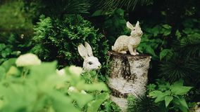 Cool figures of hares in the garden. Lovely garden decoration. House territory stock footage