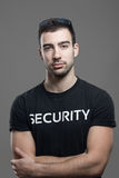 Cool fit security guard in black shirt with crossed arms looking at camera Royalty Free Stock Image