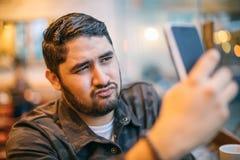 Flirtatious selfie taking man on mobile phone. Online communication dating Stock Image