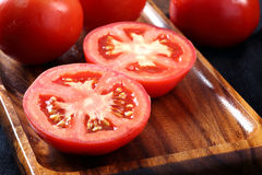 Cool fresh tomatoes, whole and half on wooden tray and wooden ba Stock Photos