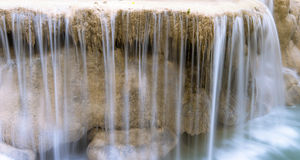 Cool fresh water falls from wet stone edge. Natural spring river Royalty Free Stock Image
