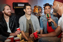 Cool Friends Chilling in Night Club Drinking Beer Stock Photos