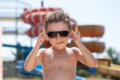 Cool funny cute kid in sunglasses in water park in summer sunny day Stock Photography