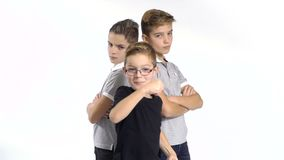 Cool gang of three brothers at white background. Cool gang of three boys at white background. Boys from both sides looks seriously at camera and holds their stock footage