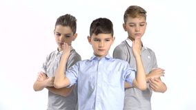 Cool gang of three little brothers at white background. Cool gang of three boys at white background. Boys from both sides looks seriously at camera and holds stock footage