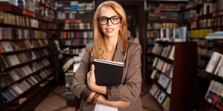 Cool geeky girl in bookshop Stock Photo