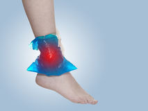 Cool gel pack on a swollen hurting ankle. Stock Photography