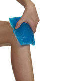 Cool gel pack on a swollen hurting knee. Stock Photo