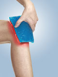Cool gel pack on a swollen hurting knee. Royalty Free Stock Photography