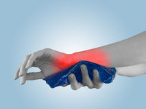 Cool gel pack on a swollen hurting wrist. Royalty Free Stock Images