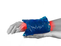 Cool gel pack on a swollen hurting wrist. Royalty Free Stock Image