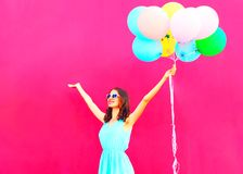 Cool girl with an air colorful balloons is having fun in summer. Over pink background Stock Photography