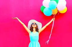 Cool girl with an air colorful balloons is having fun in summer. Over pink background Royalty Free Stock Photo